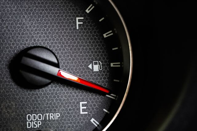 close up of car fuel gauge with red needle