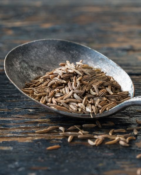 close up of caraway seeds in old spoon on wooden table