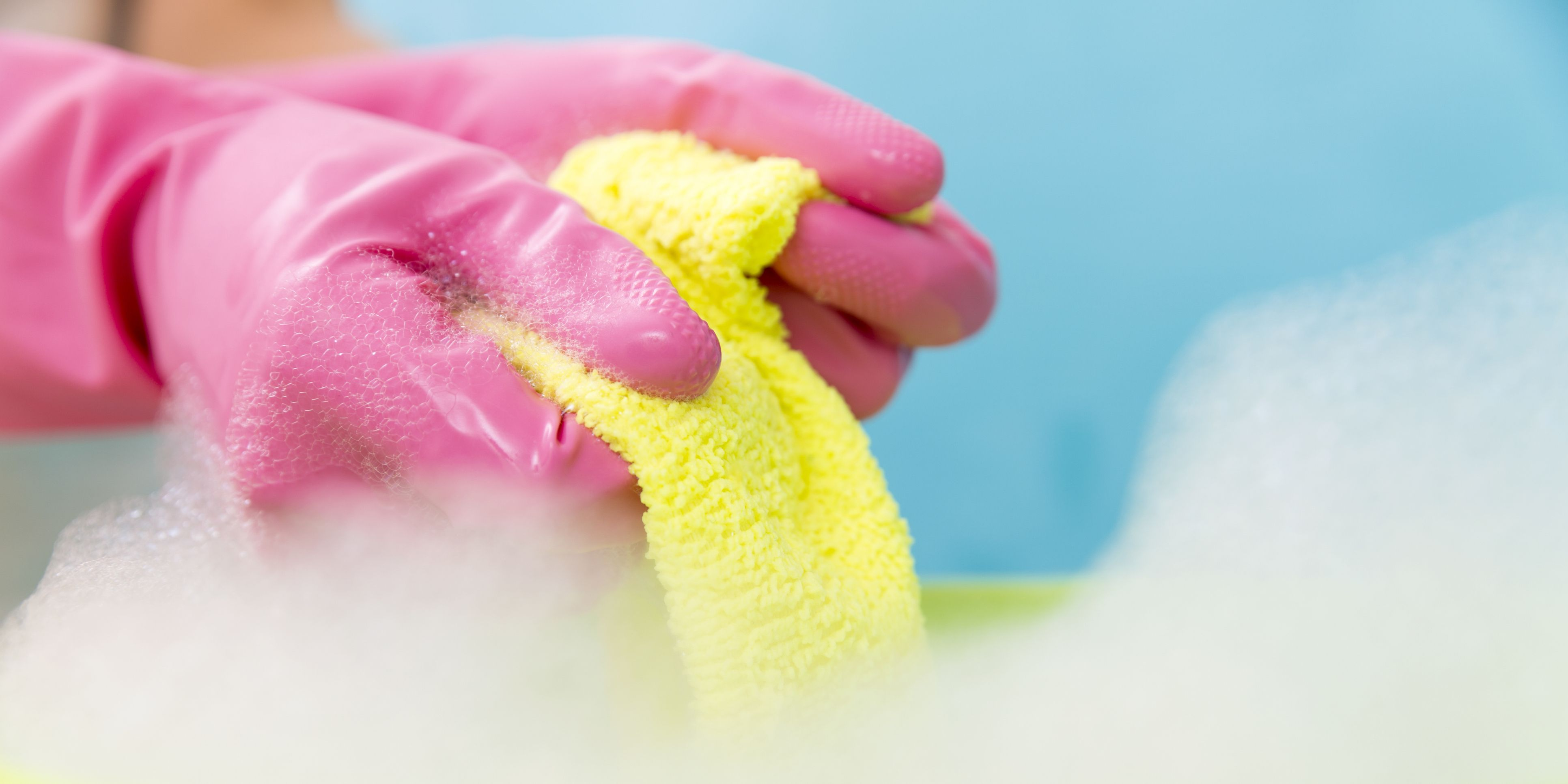 Close-up of cleaner woman hand squeezing cloth in bucket filled with soap