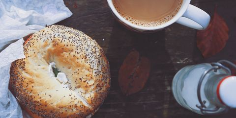 Close-Up Of Coffee Cup and poppyseed bagel