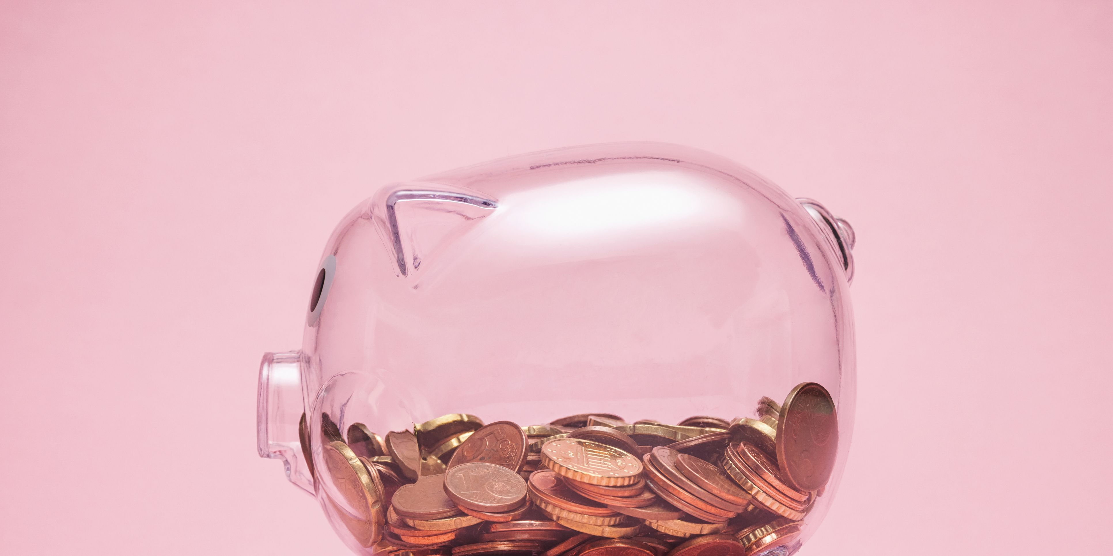 Close-Up Of Coin In Piggy Bank Against Pink Background
