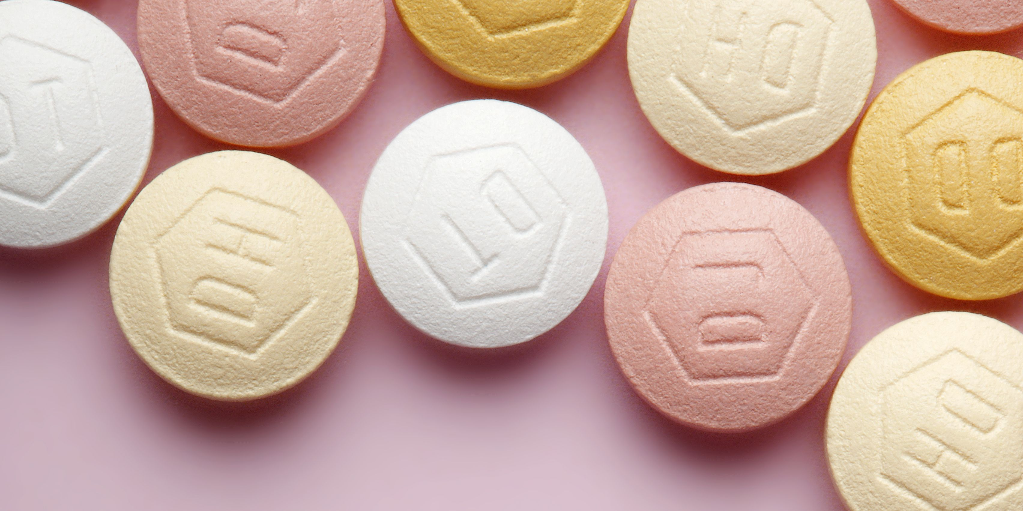 Close up of contraceptive pills on a pink surface