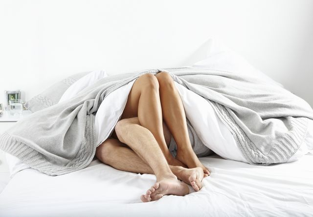 closeup of couple's legs in bed together