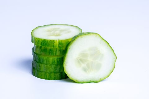 Close-Up Of Cucumber Slices Against White Background
