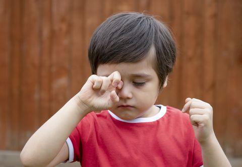 close up of cute boy rubbing eye