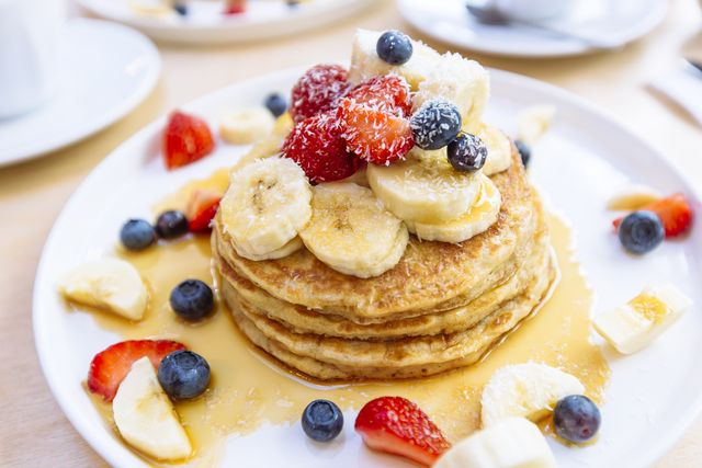 close up of delicious pancakes with fresh fruits berries and maple syrup on a plate