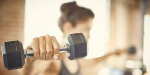Close-up of dumbbell held by young woman in gym
