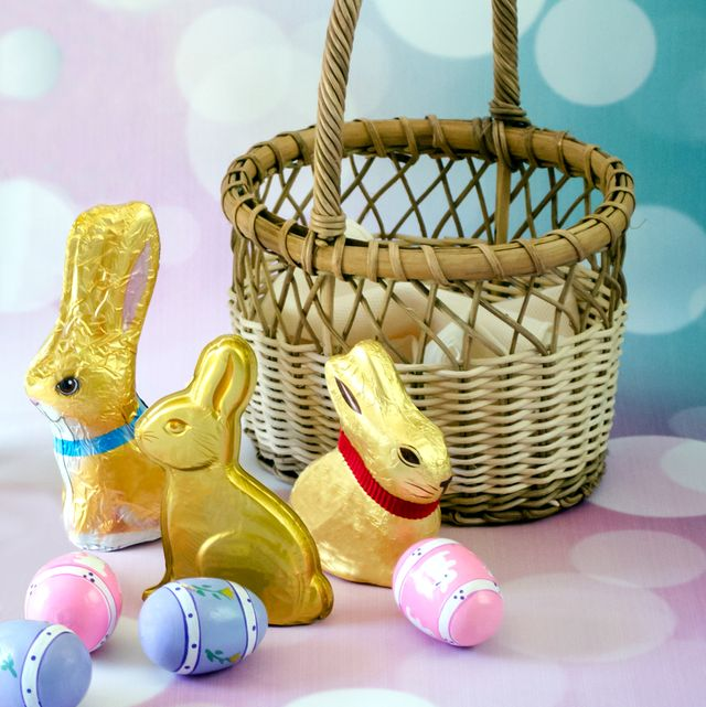 close up of easter bunnies with eggs and wicker basket against abstract backgrounds
