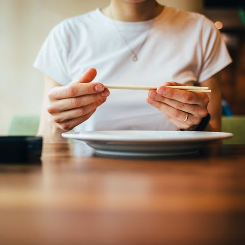 close up of female hands holding chopsticks