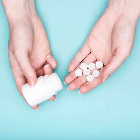 Close up of female hands holding medication bottle and white pills over pastel blue background. Patient taking medication.
