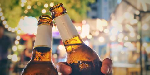 Close-Up Of Friends Toasting Beer Bottles At Night