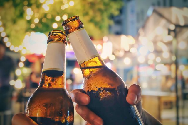 close up of friends toasting beer bottles at night