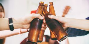 Close-Up Of Friends Toasting Beer Bottles