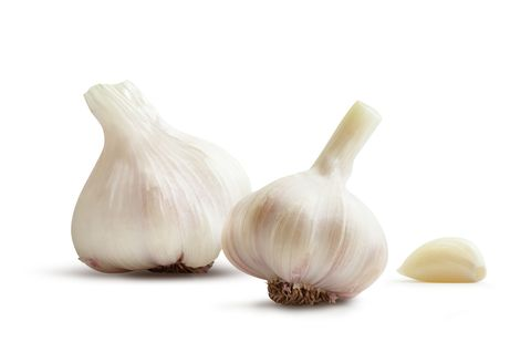 Close-Up Of Garlic Bulbs Against White Background