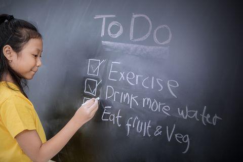 close up of girl writing on blackboard