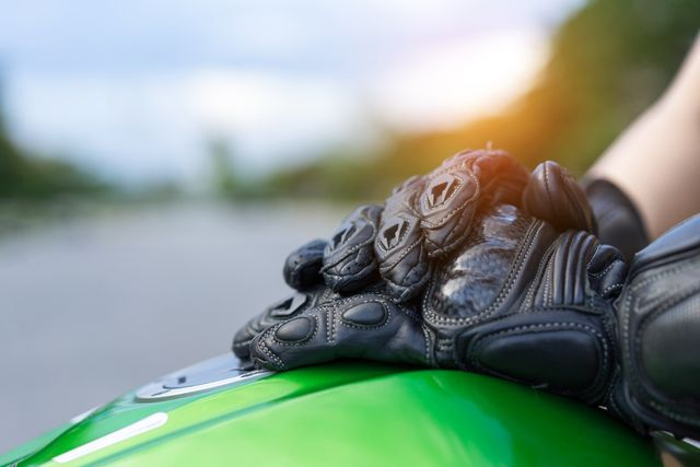 close up of gloved hands on tank of motorcycle