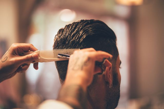 close up of hairstylist's hands cutting strand of man's hair