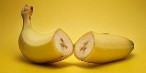 Close-Up Of Halved Bananas On Yellow Background