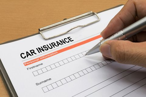 Close-Up Of Hand Filling Car Insurance Form
