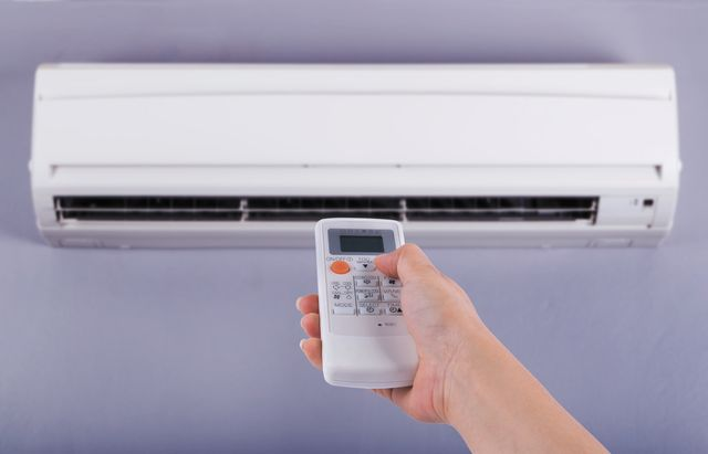 hand holding remote to air conditioner