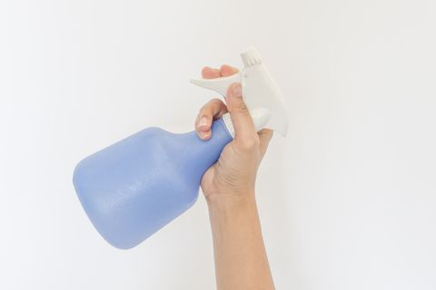 Close-Up Of Hand Holding Spray Bottle Over White Background