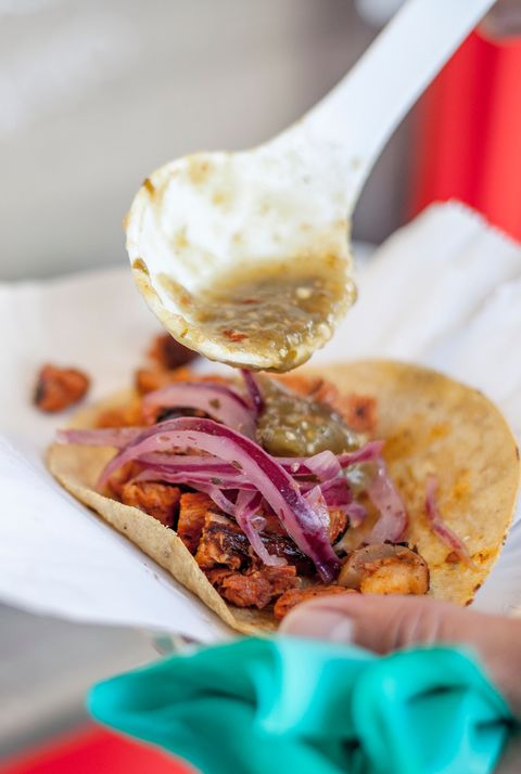 Close-Up Of Hand Holding Taco In Paper Plate