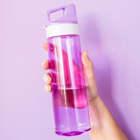 Close-Up Of Hand Holding Water Bottle Against Colored Background