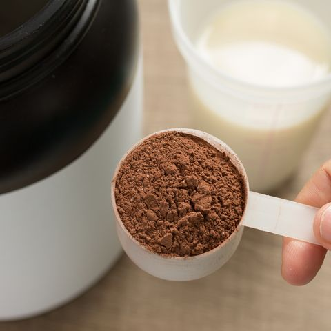 close up of hand holding whey cup on table