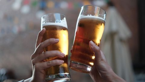Close-Up Of Hands Holding Beer Glasses