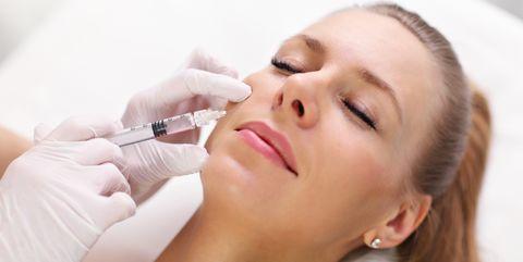 close up van cosmetisch arts die fillers injecteert bij vrouw
