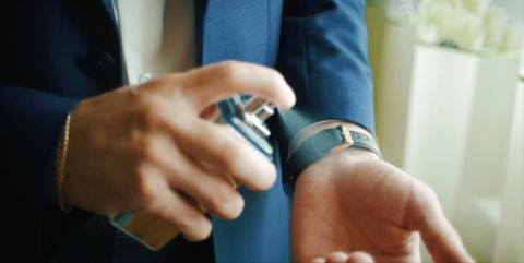 Close-up of handsome business man or groom using perfume. Clip
