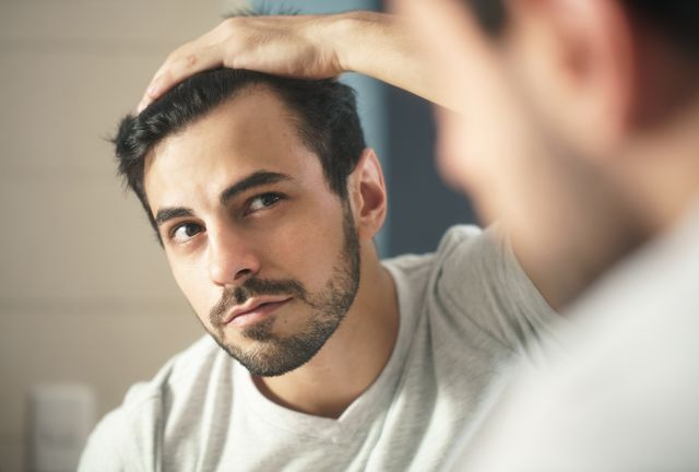 close up of handsome man looking in mirror at home