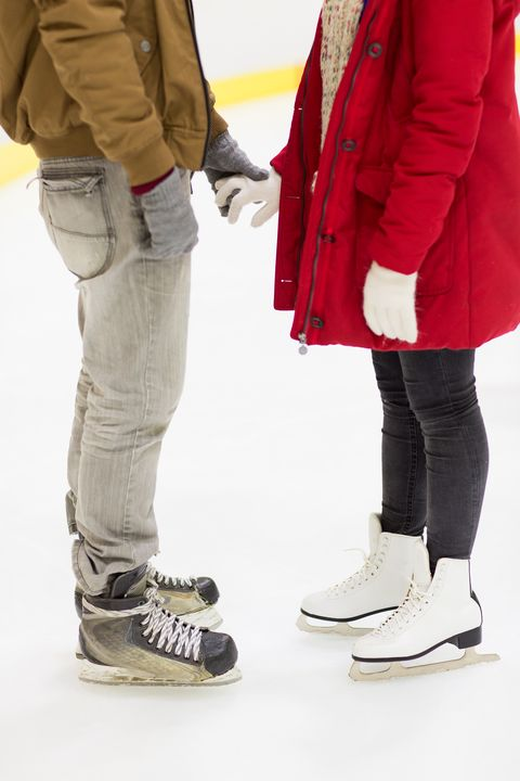 close up of happy couple skating on ice rink