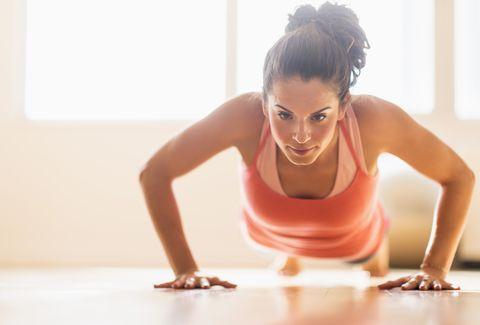 Close up of Hispanic woman doing push-ups in gym