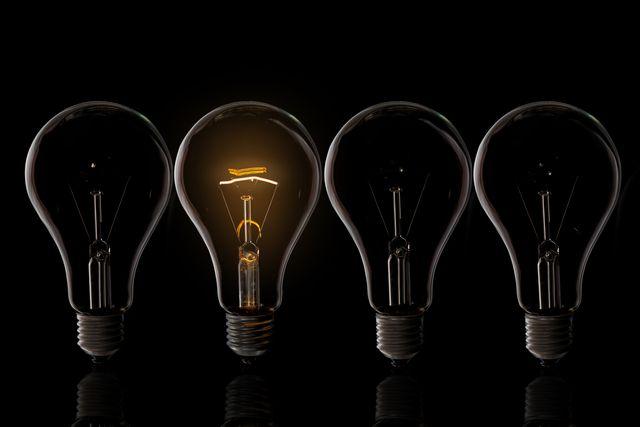close up of illuminated light bulb against black background