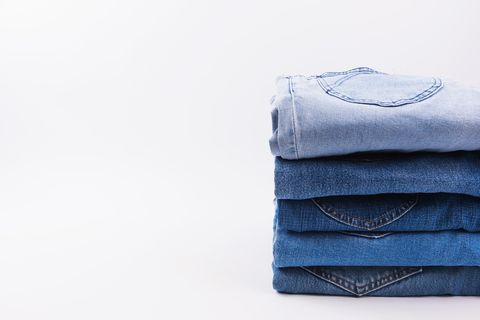 Close-Up Of Jeans Stacked Against White Background
