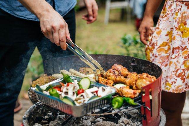 close up of man cooking food on bbq