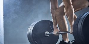 Close-up of man doing deadlift exercise at gym