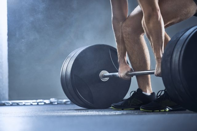 close up of man doing deadlift exercise at gym