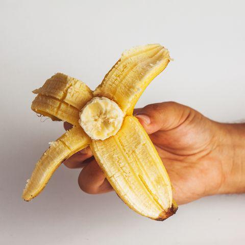 Close-Up Of Man Holding Banana Against White Background