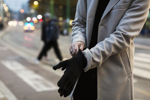 Close-up of man in the city putting on gloves