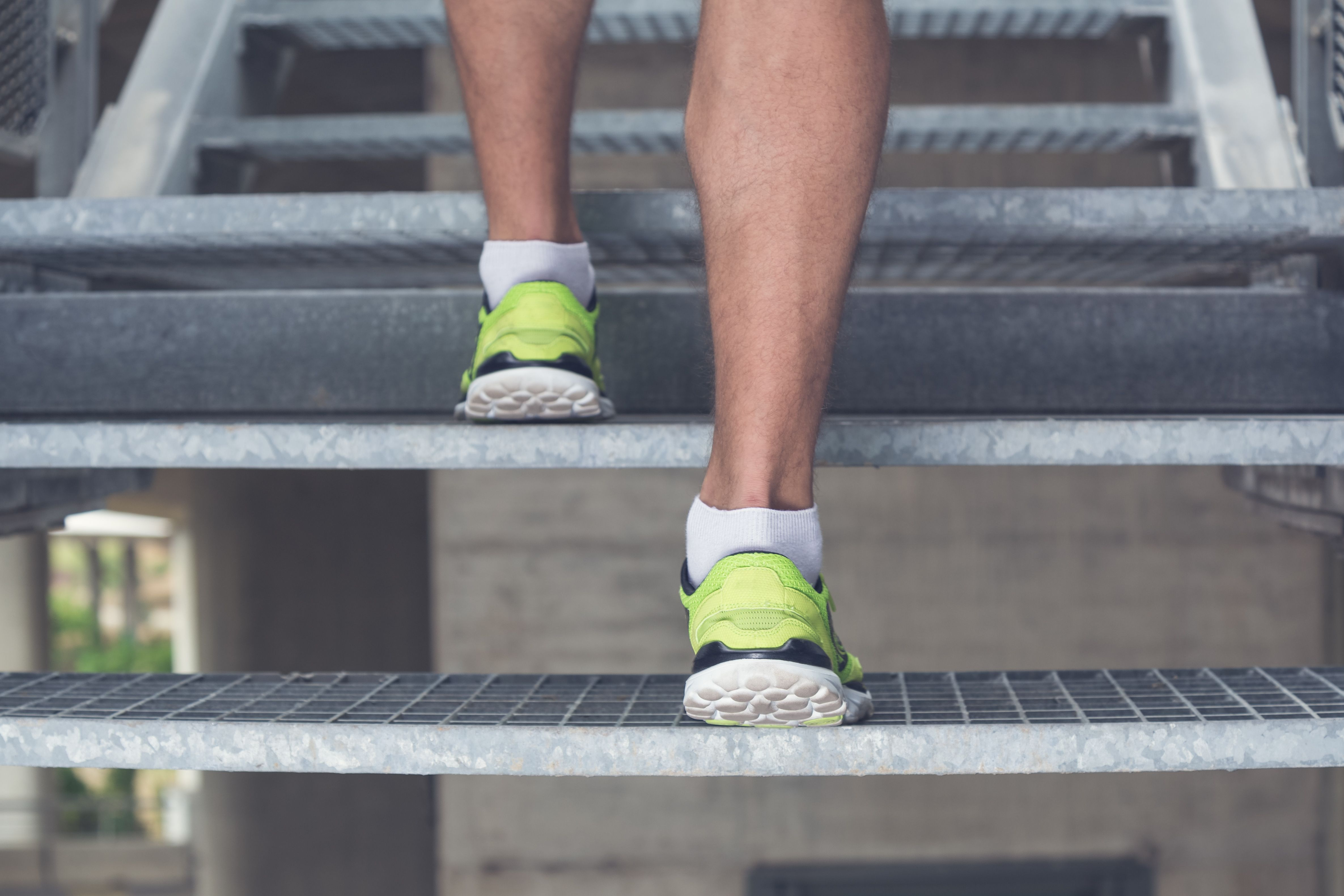 Close up of man legs with sneakers running up the stairs. Sport, fitness, jogging, workout and healthy lifestyle concepts.