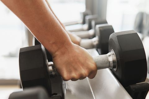 close up of man using dumbell