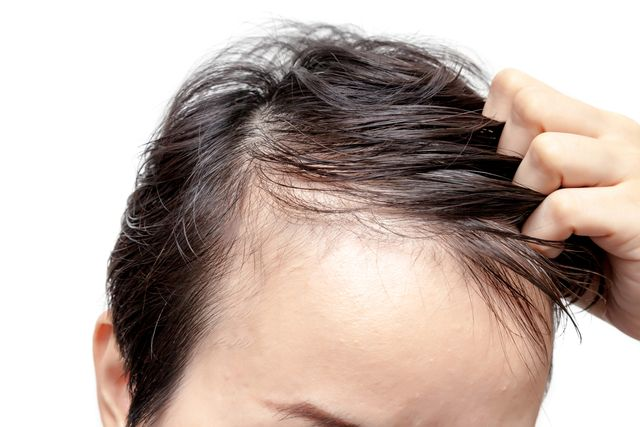 close up of man with hand in hair against white background