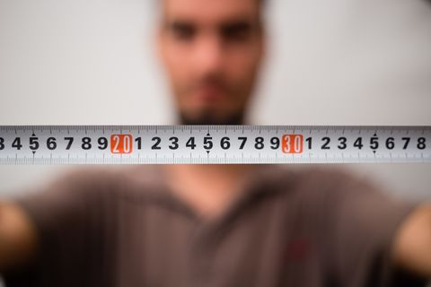Close-Up Of Man With Tape Measure