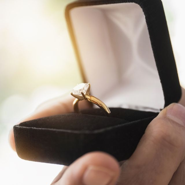 close up of mans hand holding open box with engagement ring