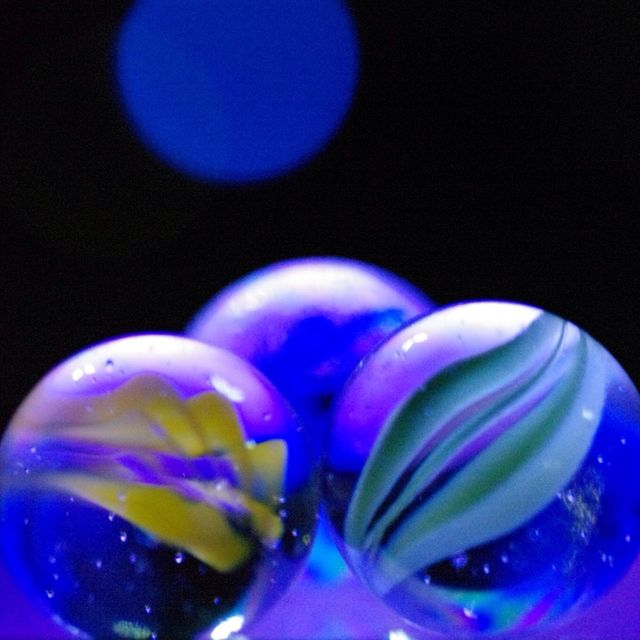 close up of marbles with reflection on glass against black background