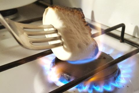 Close-Up Of Marshmallow Roasted On Gas Stove Burner