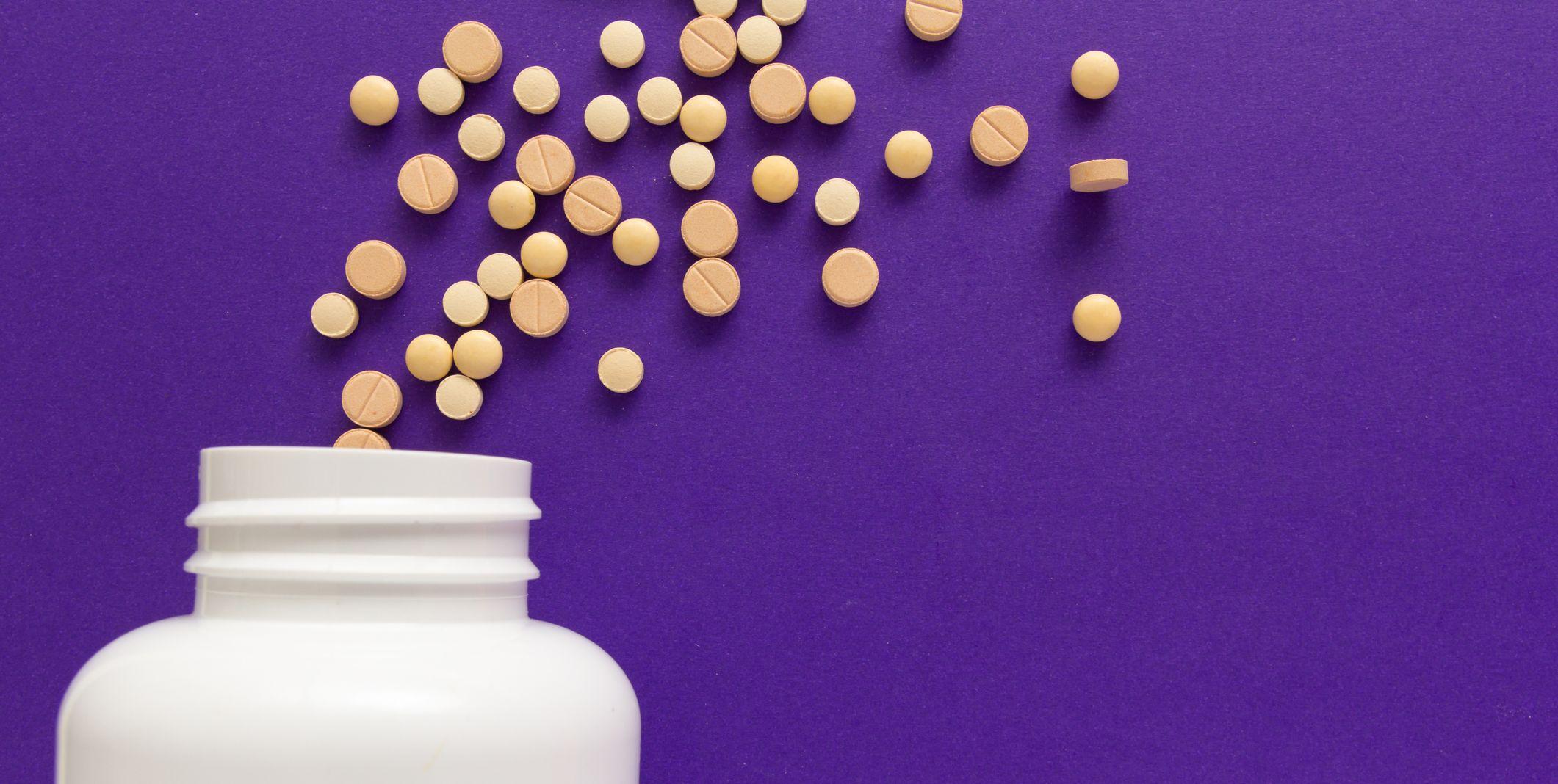 Close-Up Of Medicine Bottle Over Violet Background