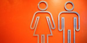 Close-Up Of Metallic Restroom Sign On Orange Wall